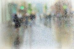 赶紧在城市街道下的人抽象背景在雨天 故意行动迷离 季节的概念 免版税库存照片