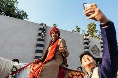赶走与客人selfie的印地安新郎白马准备好印地安婚礼在曼谷,泰国 免版税库存图片