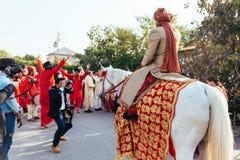 赶走与黄色和红色样式织品、花项链和红色头巾的印地安新郎白马有客人的 图库摄影