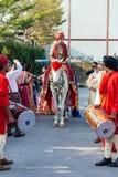 赶走与黄色和红色样式织品、花项链和红色头巾的印地安新郎白马有客人的 免版税库存照片