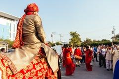 赶走与黄色和红色样式织品、花项链和红色头巾的印地安新郎白马有客人的 免版税库存图片