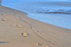 起动,在沙子的鞋子印刷品与太阳光 在波儿地克的海滩的足迹 库存图片