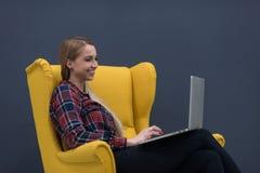 起始的事务,妇女研究膝上型计算机和坐黄色 免版税库存图片