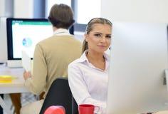 起始的事务,年轻美丽的妇女当研究计算机的软件开发商在现代办公室 图库摄影