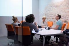 起始的企业队在现代夜办公室buildi的一次会议上 库存照片