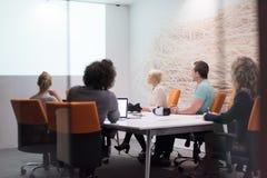 起始的企业队在现代夜办公室buildi的一次会议上 免版税库存照片