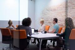 起始的企业队在现代夜办公室buildi的一次会议上 图库摄影
