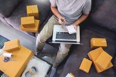 起始的小企业SME,企业家所有者使用智能手机或笔记本采取接受和检查网上购买购物 免版税库存照片