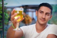 起来年轻的人在酒吧的一块玻璃 库存照片