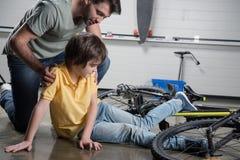 起来从的父亲帮助的受伤的儿子 免版税库存照片