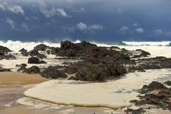 起泡沫涌起往与风雨如磐的海的岸 库存图片
