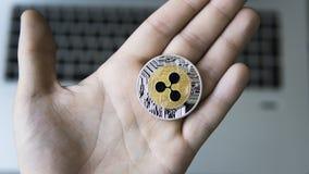 起波纹在一个膝上型计算机键盘特写镜头的硬币在矿工手上 Blockchain采矿 数字式金钱和真正cryptocurrency 免版税库存图片