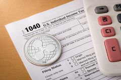起波纹在1040报税表的物理银币标志与计算器 免版税库存照片