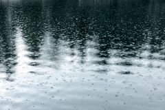 起波纹湖表面上的雨珠在雨期间 免版税图库摄影