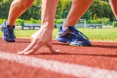 起点 准备好的赛跑者去紧密  准备好平稳去概念 在巨大体育事业初 手接触 库存照片