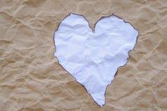 起皱纹的纸切口和灼烧的心脏形状 免版税库存图片