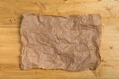 起皱纹的纸在木背景 免版税图库摄影