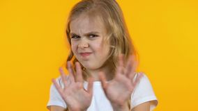 起皱纹鼻子和拒绝从不健康的甜点,黄色背景的女孩 股票视频