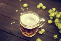 起草在玻璃瓶子的冰镇啤酒有在黑色的绿色成熟啤酒花球果树的 免版税库存照片