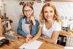 起草他们的咖啡馆的母亲和女儿一个经营计划 库存图片