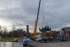 起重机举的nlue猛拉小船到在RSC前面的运河里 图库摄影