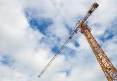 起重机和工作者建造场所的有蓝天背景 免版税库存照片