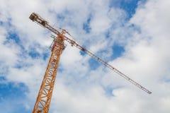 起重机和工作者建造场所的有蓝天背景 免版税库存图片