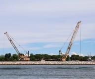 起重机和建造场所在建造的水坝海 免版税库存照片