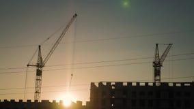 起重机和楼房建筑站点日落的 天空的背景的剪影工作者 影视素材