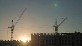 起重机和楼房建筑站点日落的 天空的背景的剪影工作者 股票视频