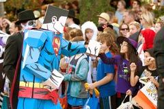 超人漫画人物拳头碰撞孩子在万圣夜游行 免版税图库摄影