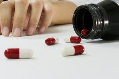 超剂量吸毒者手,在地板上的药物麻醉注射器 库存照片