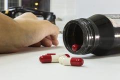 超剂量吸毒者手,在地板上的药物麻醉注射器 免版税库存照片