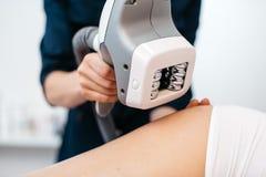 超声波气蚀mashine在美容师的手上 关闭上色百合软的查阅水 妇女得到反脂肪团治疗 免版税图库摄影