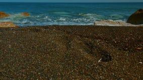 超广角滑子被射击与黑沙子和人的脚印的地中海火山的海滩 股票录像