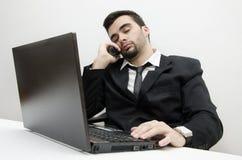 超时工作在手表的年轻商人焦点 免版税库存照片
