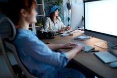 超时微笑和工作在工作场所的现代妇女设计师 免版税库存照片