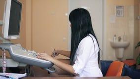超省波心动描记术和超生波检查法在医生` s办公室:审查耐心` s心脏的女性医生通过使用  股票录像