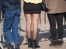 超短裙和腿在黑裤袜 免版税库存图片
