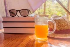 超级保护免受太阳 晒斑风险概念 伞保护的美女事 书,太阳镜,橙汁过去 免版税库存图片