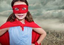 超级女孩戴着红色面具的站立用在臀部的手的画象和海角反对都市风景backgro 免版税库存照片