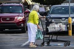 超级市场停车场的小老妇人与使用为技巧的购物车和音乐家在背景中 库存照片
