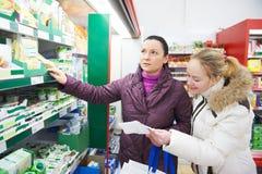 超级市场牛奶店购物的二名妇女 免版税库存图片