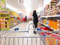 超级市场的妇女有台车的 库存图片