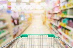 超级市场走道有购物车迷离背景 免版税库存照片