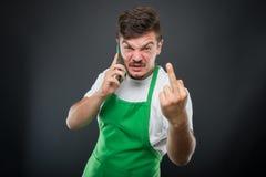 超级市场雇主谈话在显示淫秽姿态的电话 免版税库存照片