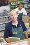 超级市场雇员和结算离开助理 免版税图库摄影