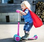 超级英雄使用滑行车可爱的概念的男婴 库存照片