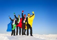 超级英雄在冬天举的队胳膊 免版税库存照片