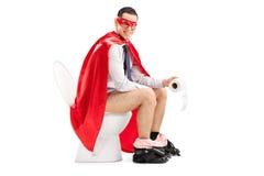超级英雄坐洗手间 免版税库存照片